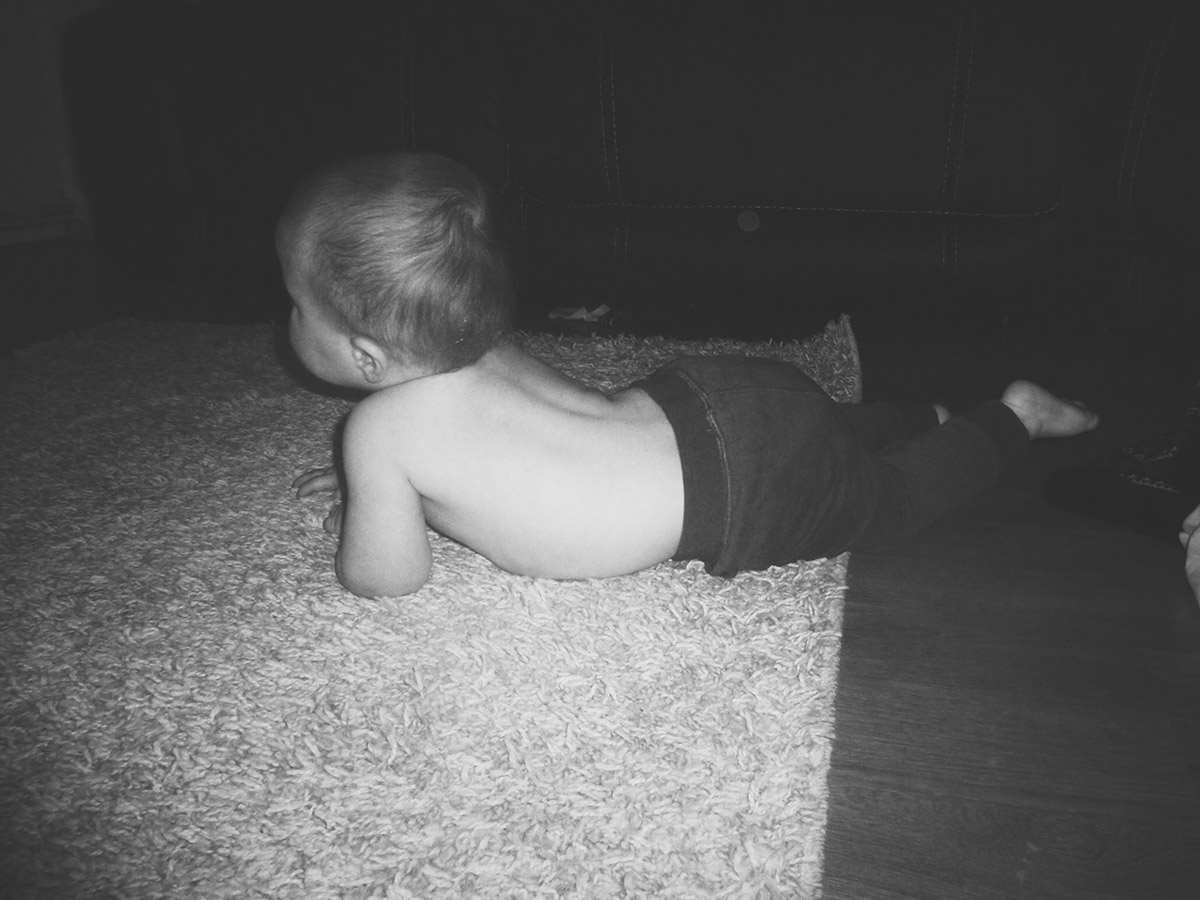 13 month old baby laying on floor