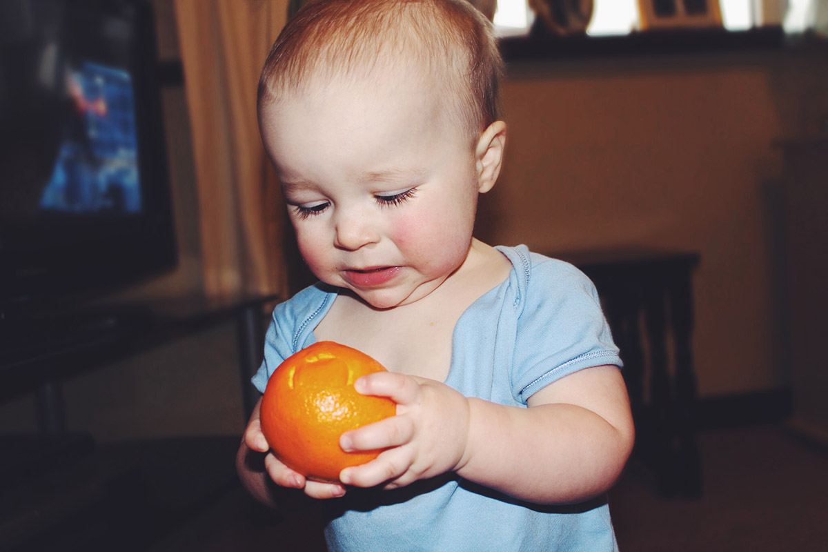 14 month old baby eating orange peel and pulling funny face