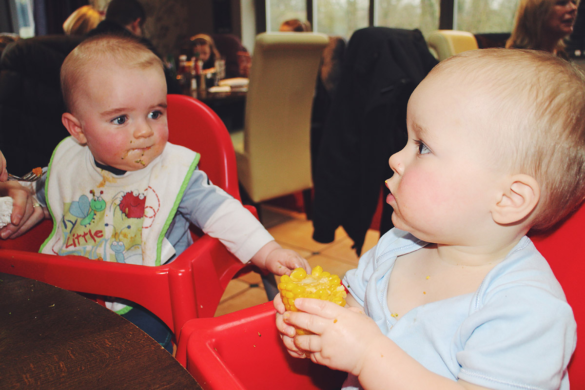 14 month old baby eating in high chair with cousin