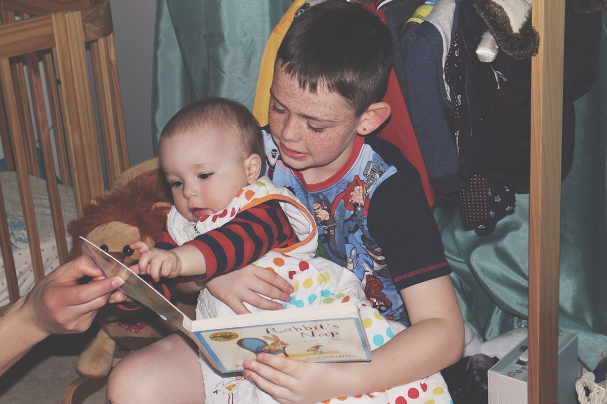 15 month old toddler reading a book with his older brother