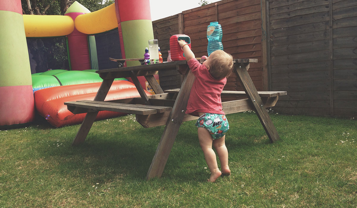 18 Months Old And Growing Up Fast - Toddler reaching up to play with bubble machine at cousins first birthday party