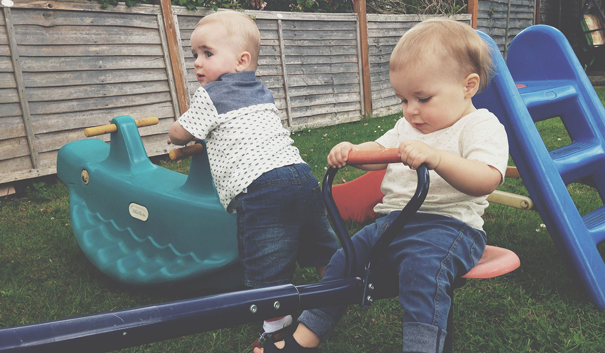 18 Months Old And Growing Up Fast - Toddler playing on the seesaw in the garden with his baby cousin