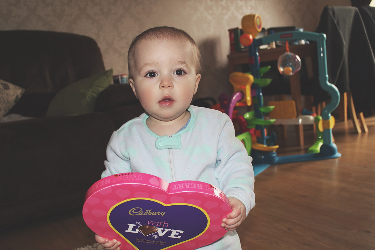 Toddler holding a box of chocolates