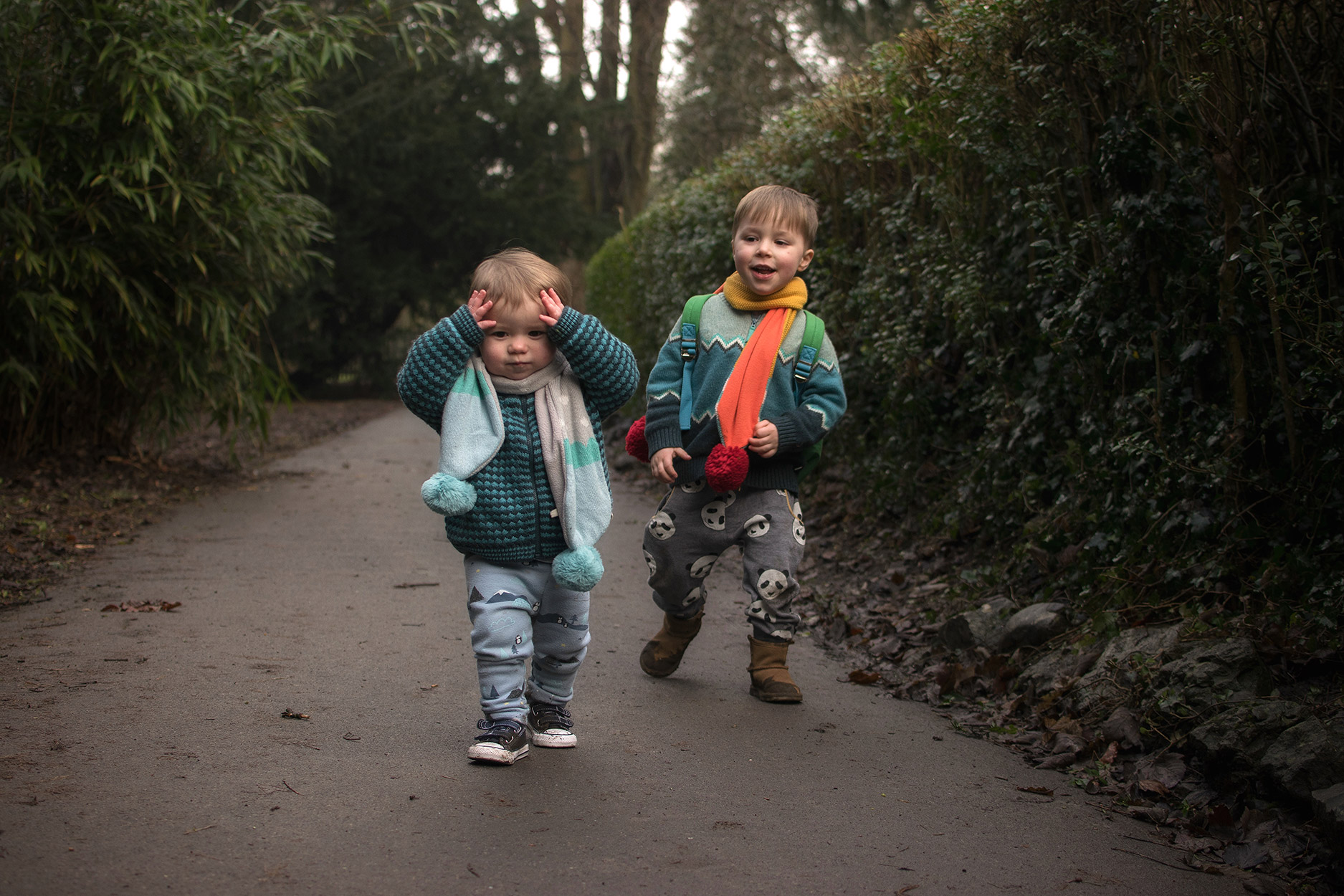 Two young brothers wearing handmade blue chevron knitwear by The Bonnie Mob, coloured Rockahula scarves and dinosaur rucksack with Mum, wearing H&M star knit jumper and black hat, adventuring in the Town Gardens