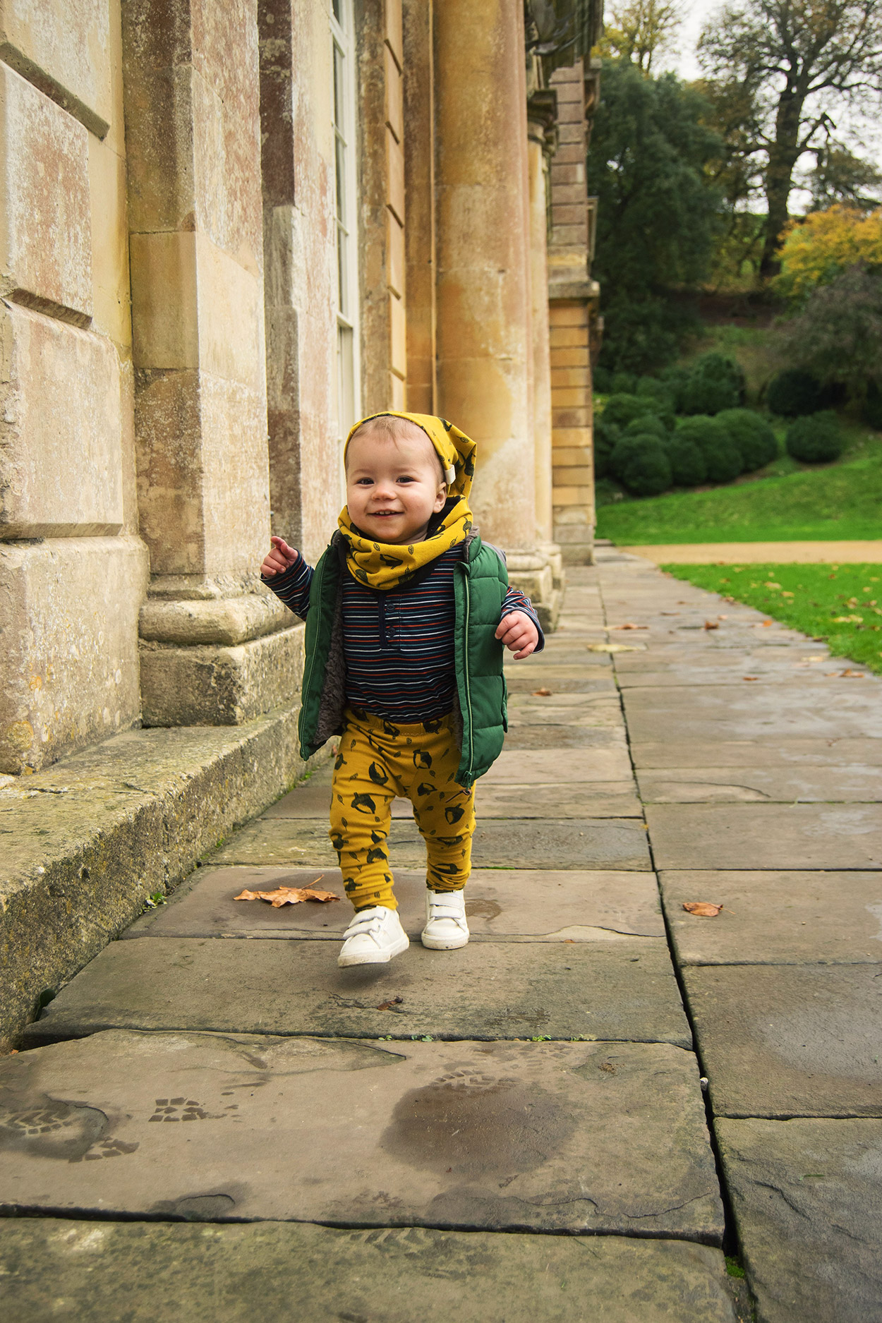 Young toddler wearing mustard acorn Bear & Babe leggings, beanie hat and snood walking along the path outside of the orangery at Durham Park, Bath