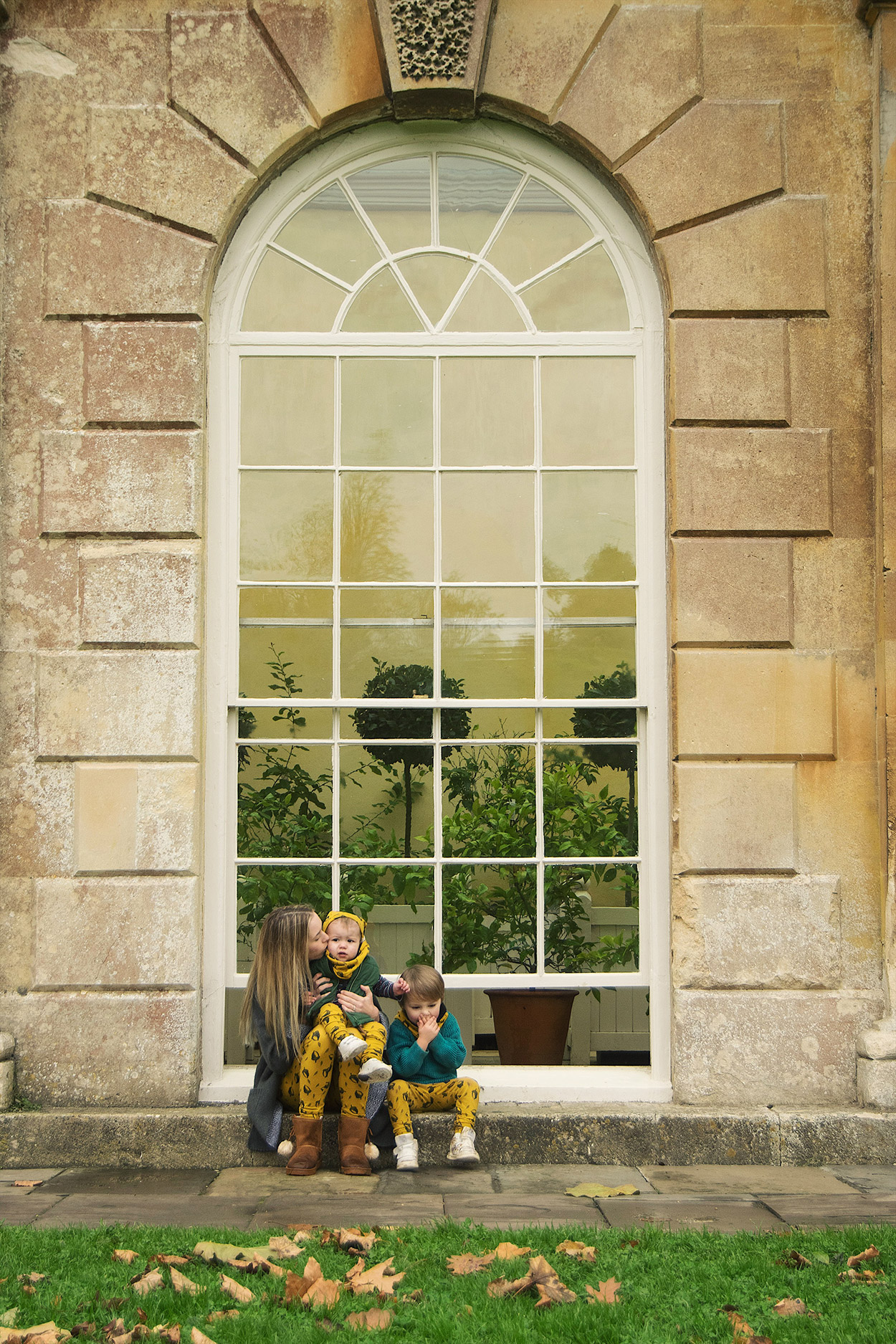 Mum and two young sons wearing twinning mustard acorn leggings posing outside the large orangery window together at Dyrham Park, Bath