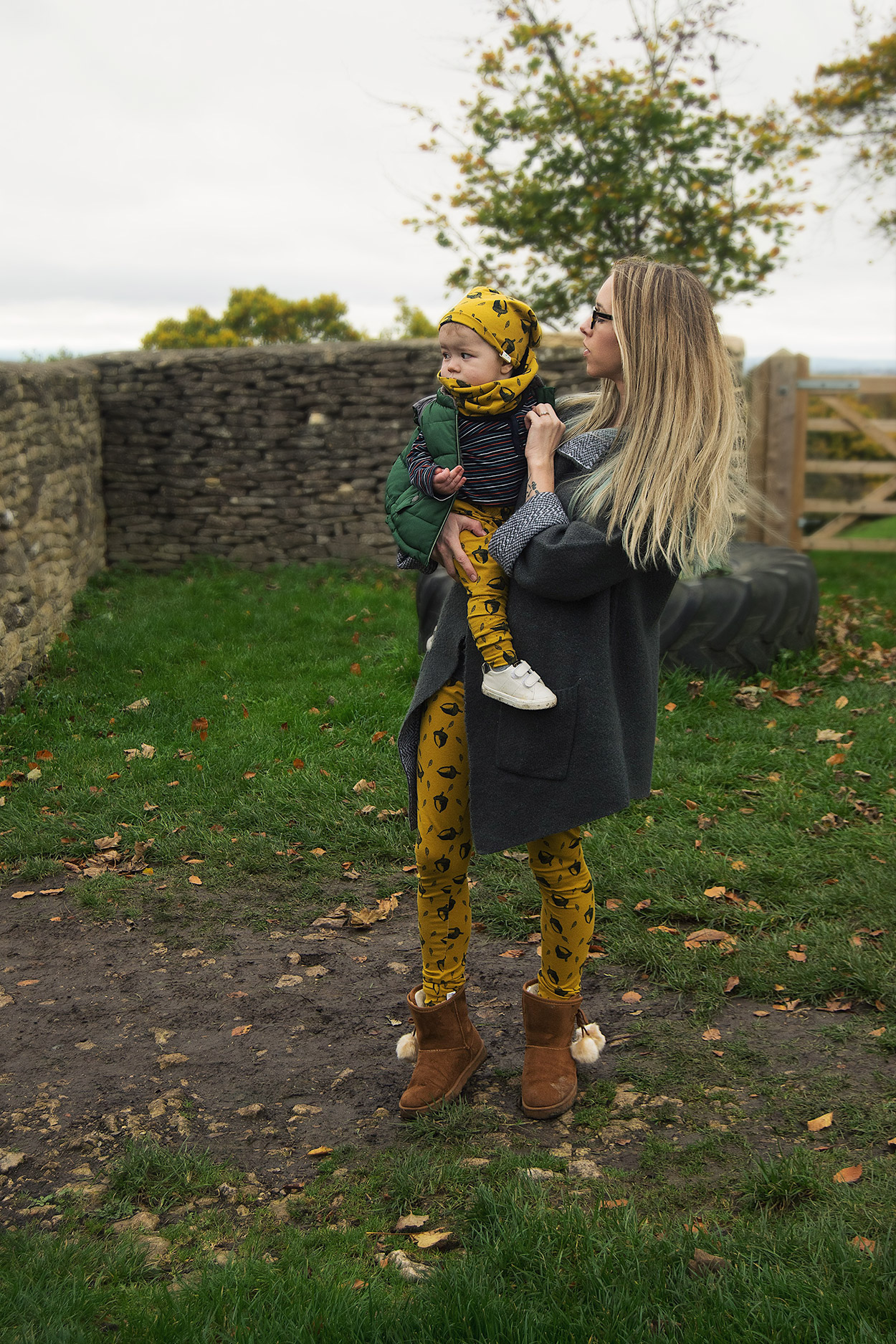 Mother and baby boy wearing mustard acorn Bear & Babe leggings and beanies looking over at Dyrham Park, Bath