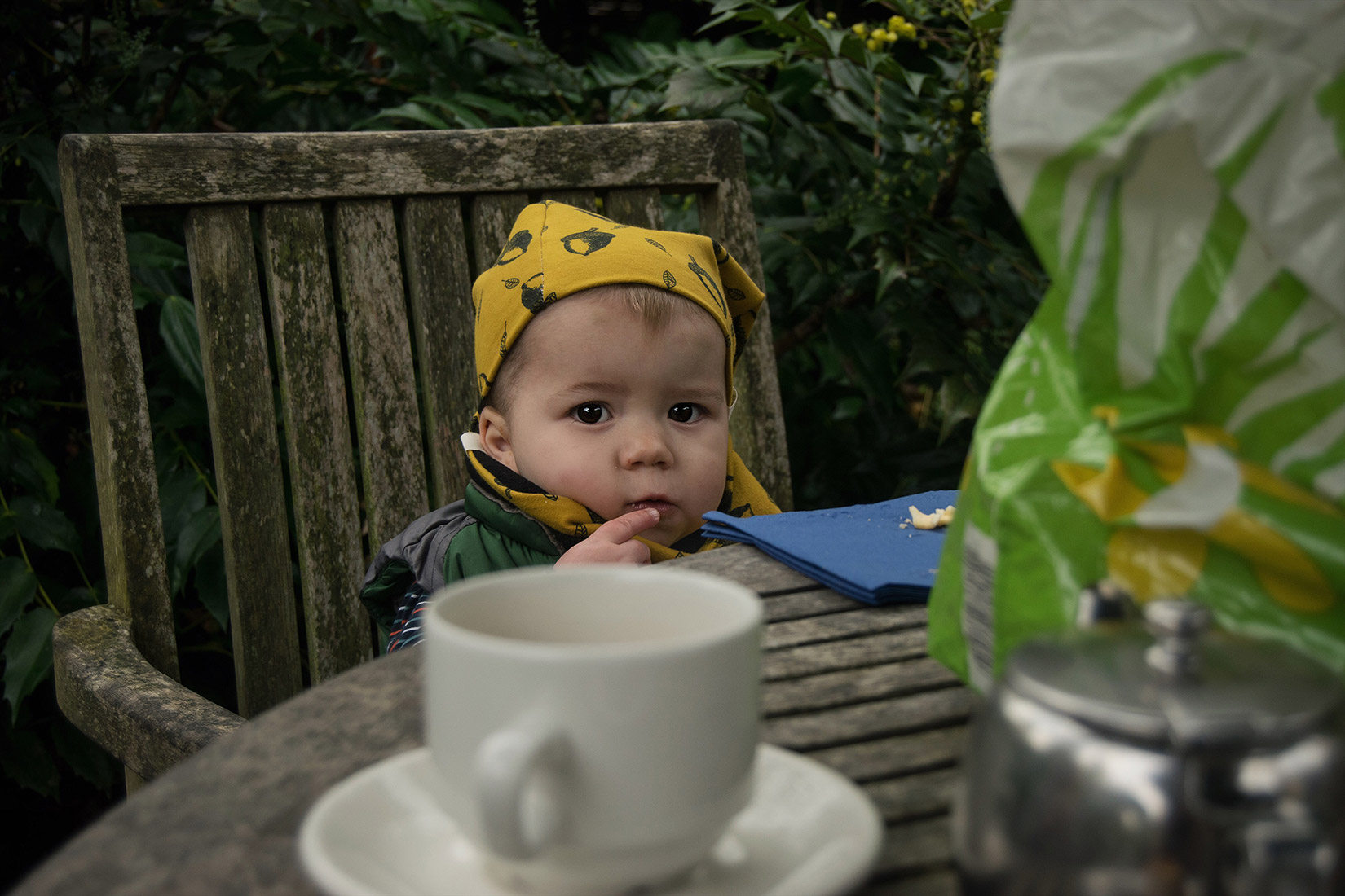 Young toddler wearing mustard acorn Bear & Babe leggings, beanie hat and snood sitting outside the cafe on a table at Dyrham Park, Bath