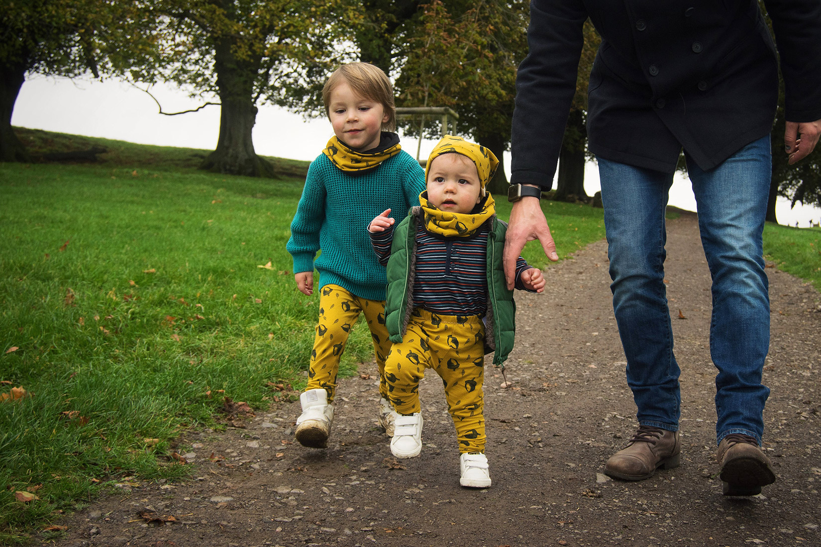 Dad walking with two young sons who are wearing matching Bear & Babe mustard acorn leggings and accessories on the Halloween trail at Dyrham Park, Bath