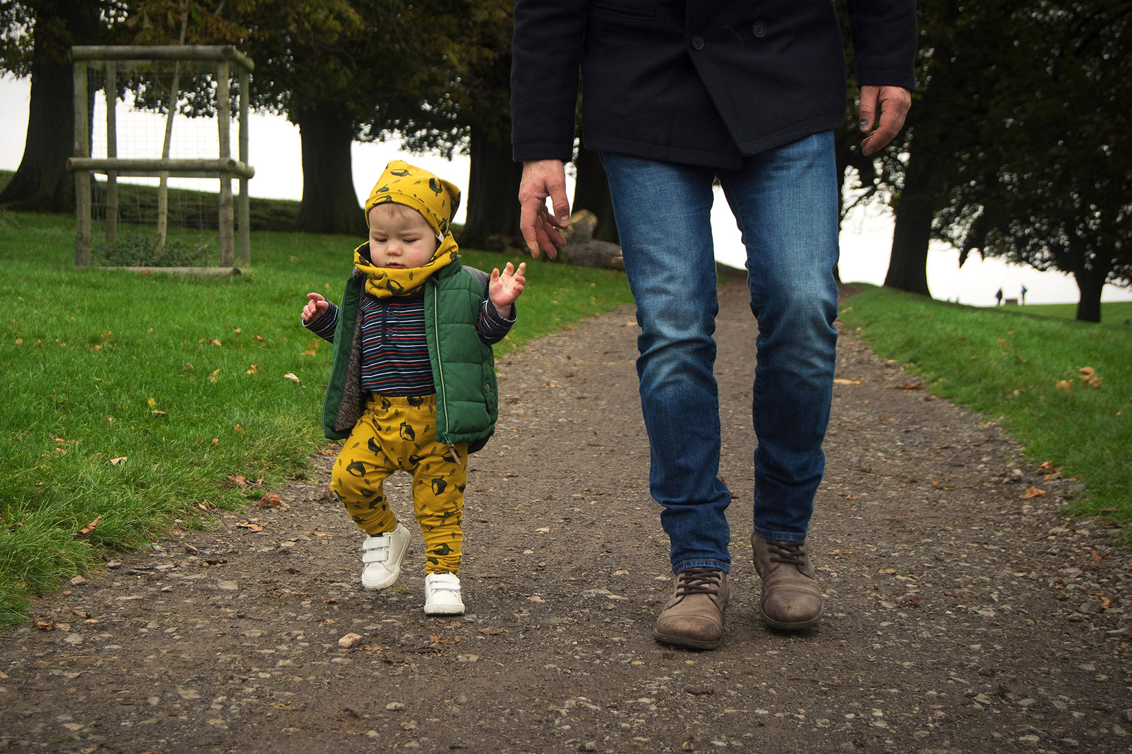 Toddler boy wearing mustard acorn leggings, beanie and snood by Bear & Babe holding Daddy's hand walking down the path on Halloween at Dyrham Park, Bath