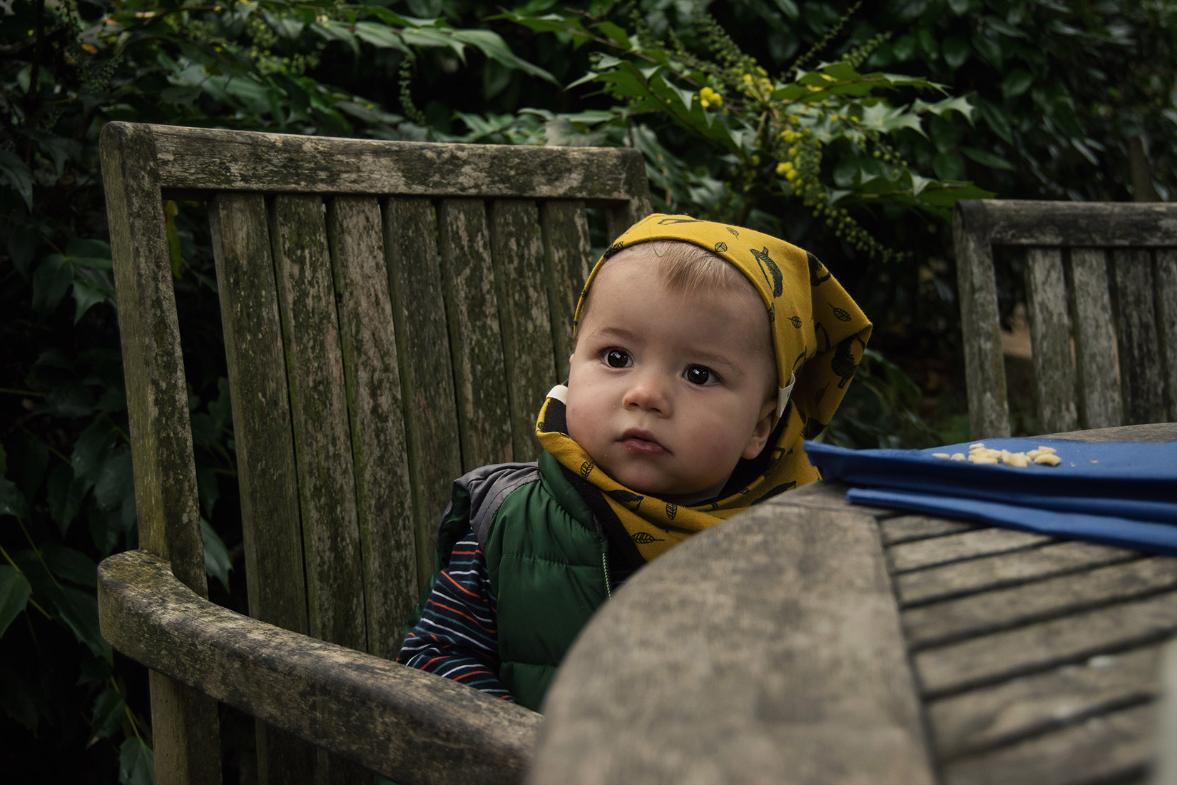 Toddler wearing Bear & Babe beanie and snood in mustard acorns print sitting at the table of the cafe at Dyrham Park nr. Bath