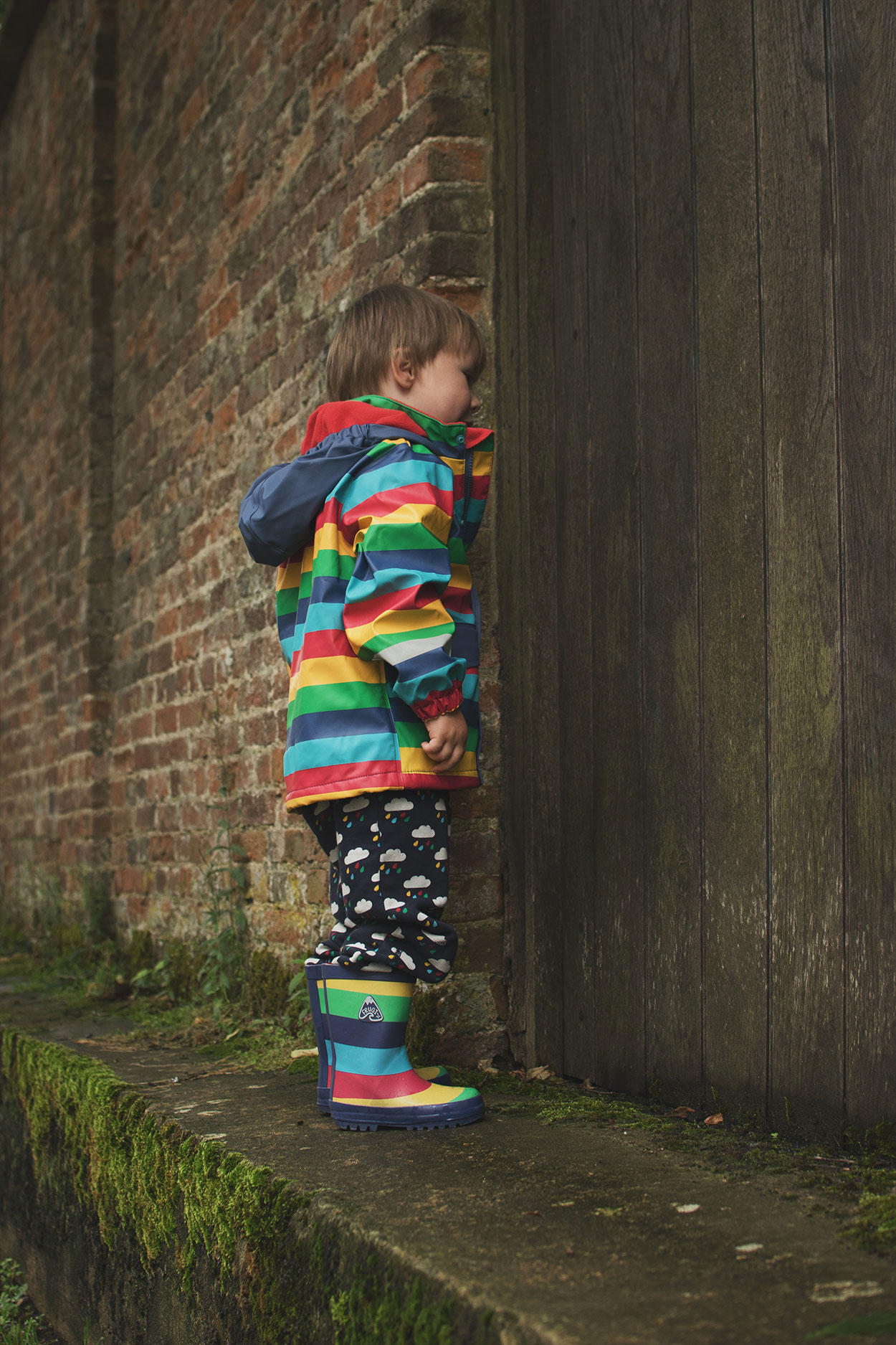Jumping in muddy puddles wearing Frugi Circus of Colour Puddle-Buster rainbow raincoat and wellies, crawlers and applique t-shirt outdoors on a rainy Summers day
