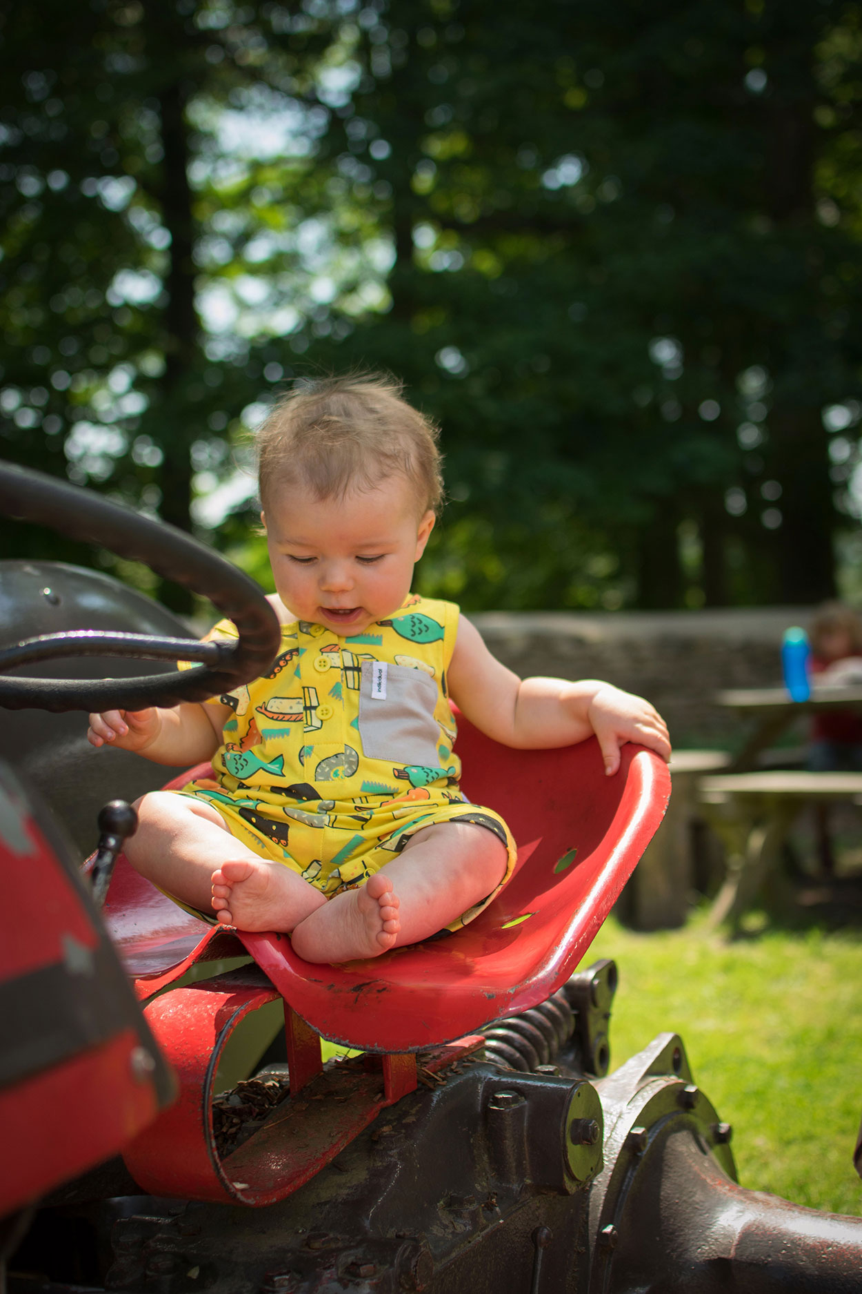 Baby wearing fun yellow chopsticks sushi playsuit from Alex and Alexa whilst sitting on a tractor at Dyrham Park, National Trust, nr. Bath