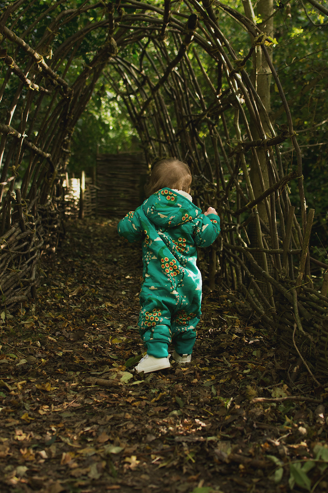 Young pre-school age boy wearing midnight peacocks pointelle top and golden cord bottoms by fair-trade and organic company Little Green Radicals with his baby brother wearing midnight peacocks snowsuit running around the hazel trail in the woods at Snowshill Manor, National Trust, the Cotswolds