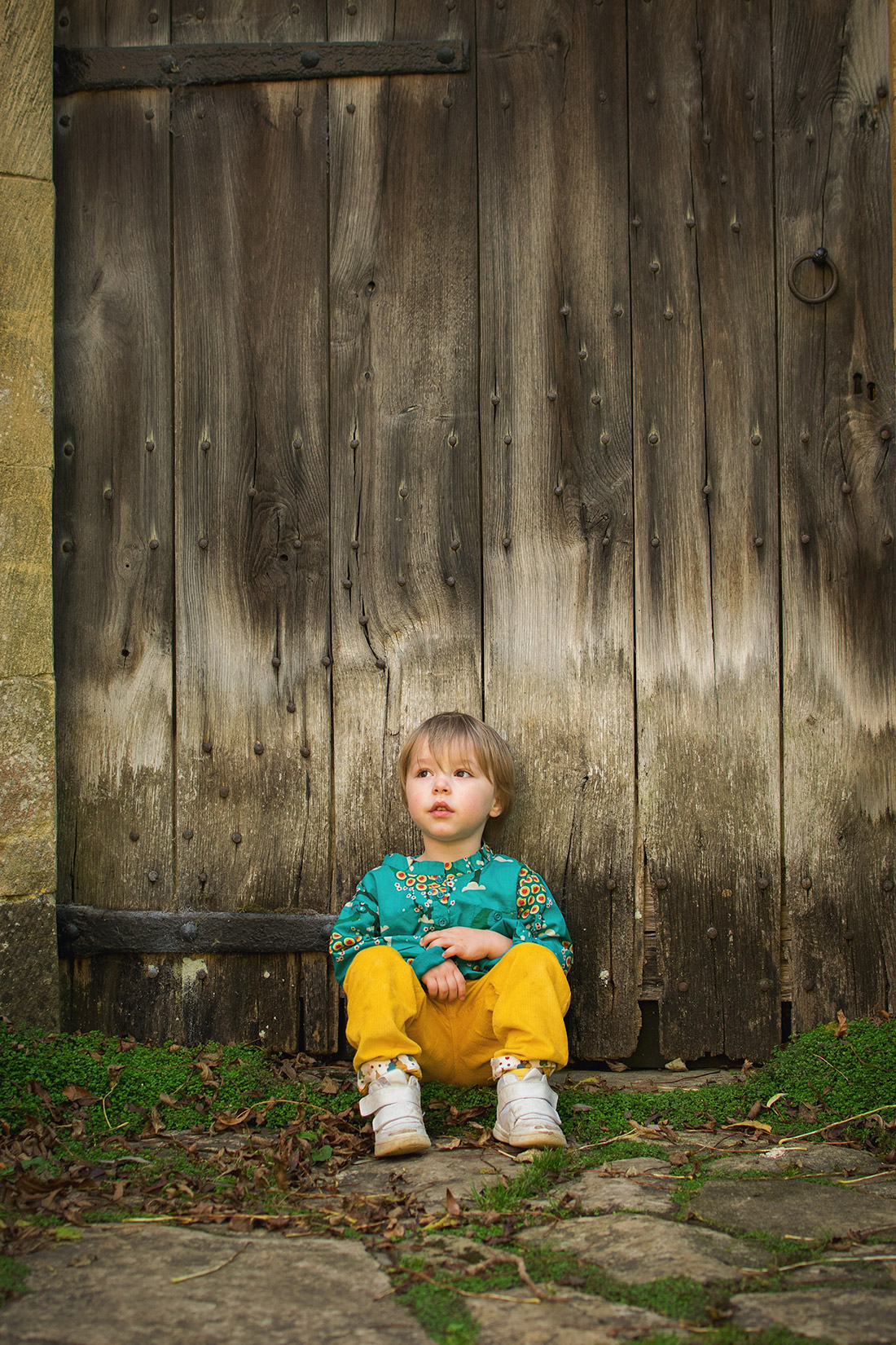 Young pre-school age boy wearing midnight peacocks pointelle top and golden cord bottoms by fair-trade and organic company Little Green Radicals whilst sitting in front of the door of Snowshill Manor, National Trust, the Cotswolds
