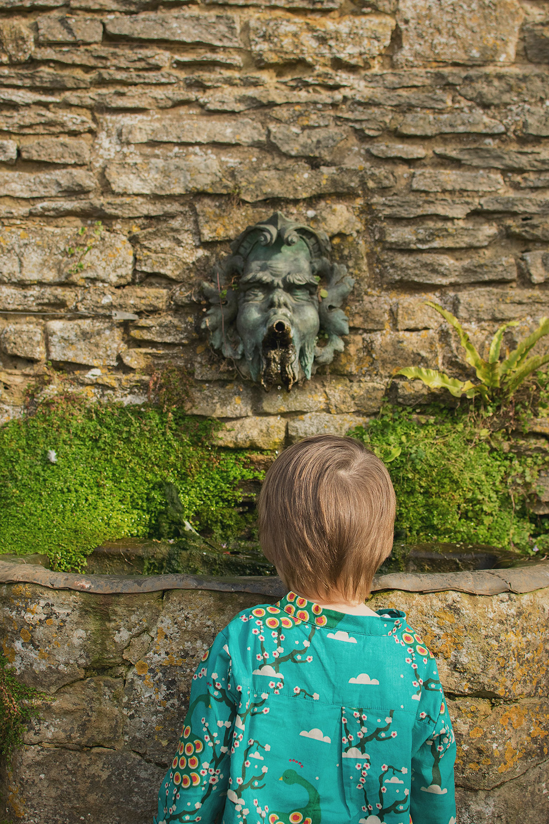 Young pre-school aged boy wearing midnight peacocks long sleeve pointelle Little Green Radicals top looking at the fountain in the gardens of Snowshill Manor, Cotswolds