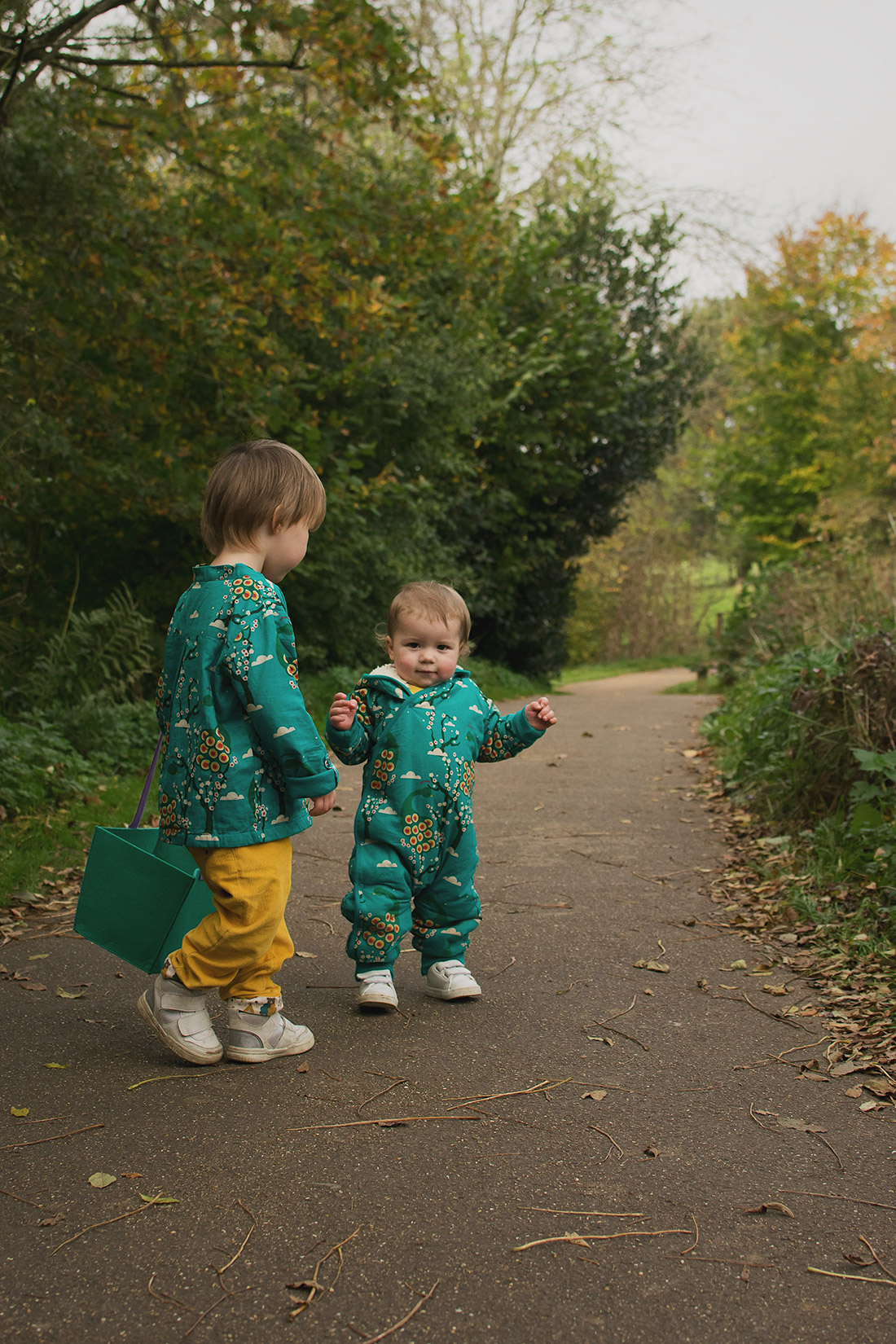 Young pre-school age boy wearing midnight peacocks pointelle top and golden cord bottoms by fair-trade and organic company Little Green Radicals with his baby brother wearing midnight peacocks snowsuit at Snowshill Manor, National Trust, the Cotswolds