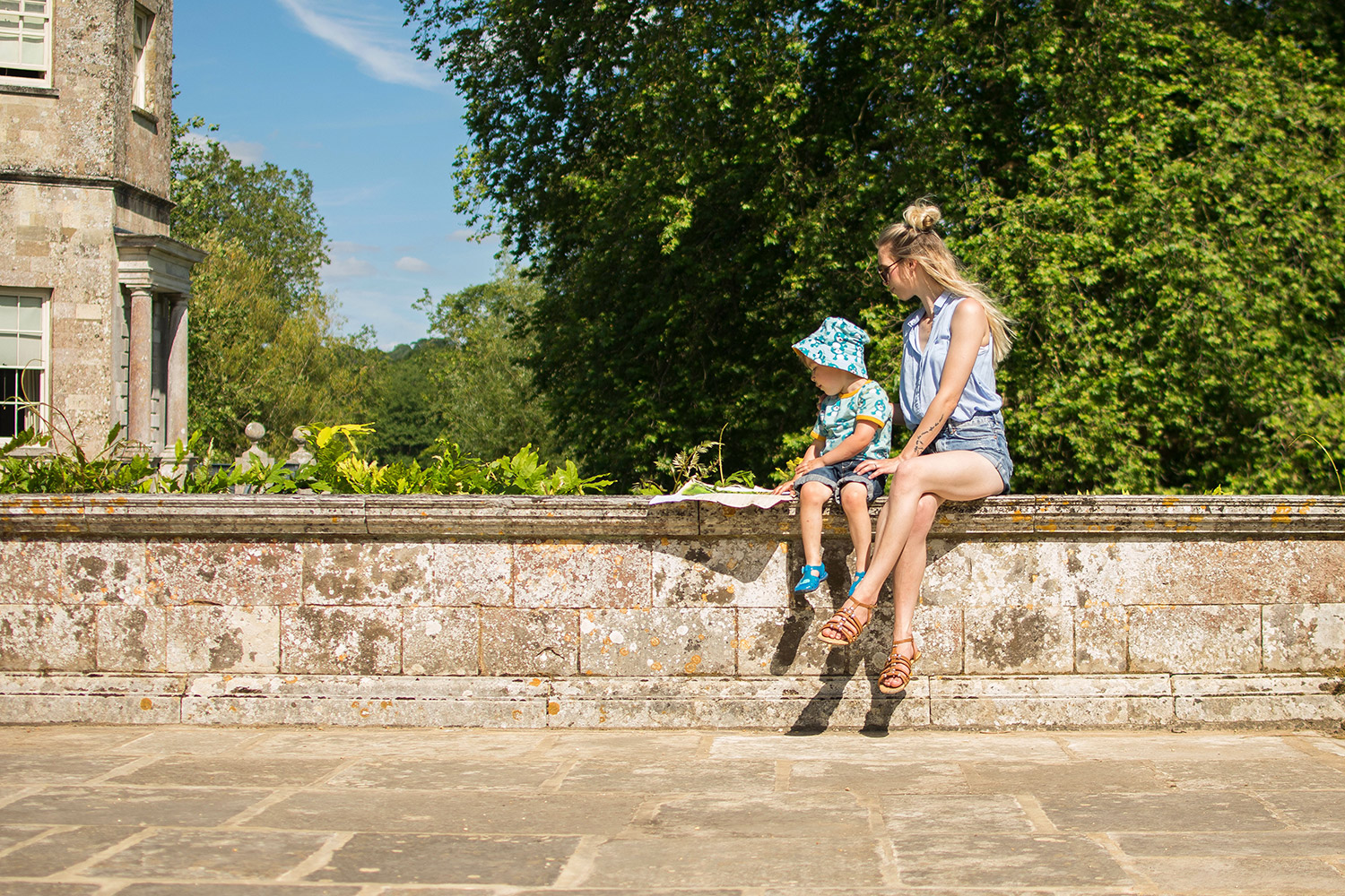 Pre-schooler and Mum sitting on the wall of Mottisfont Abbey, National Trust on a Summer's Day wearing Maxomorra seal print t-shirt and sun hat and sunglasses