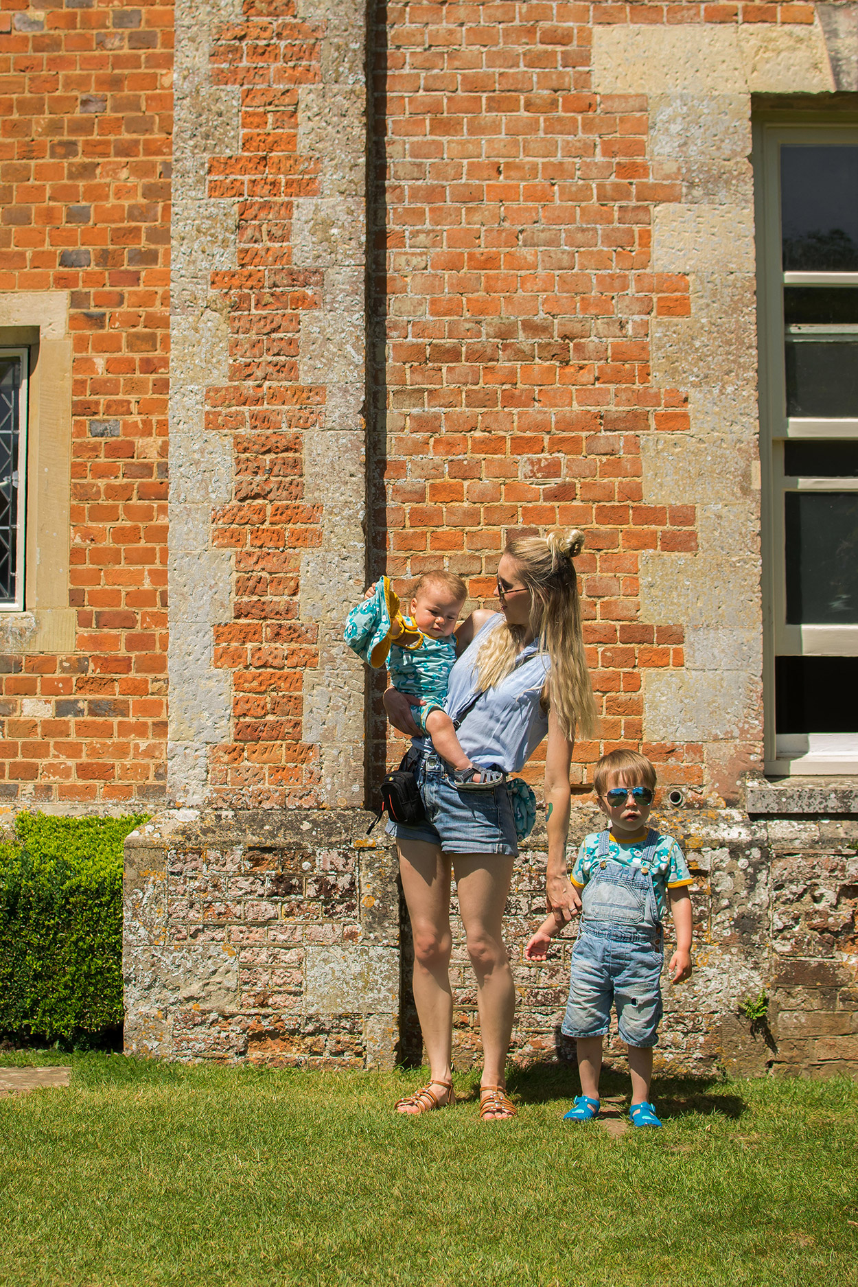 Mum and two boys standing outside Mottisfont Abbey, National Trust on a Summer's Day wearing Maxomorra seal print t-shirt, romper and sun hat and sunglasses