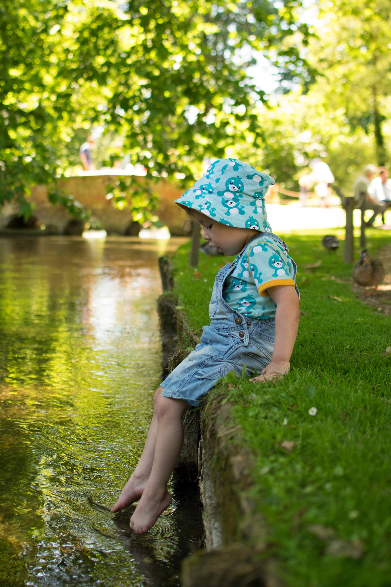 Young boy dipping his toes in the stream at Mottisfont Abbey, National Trust on a Summer's Day wearing Maxomorra seal print t-shirt, romper and sun hat and sunglasses