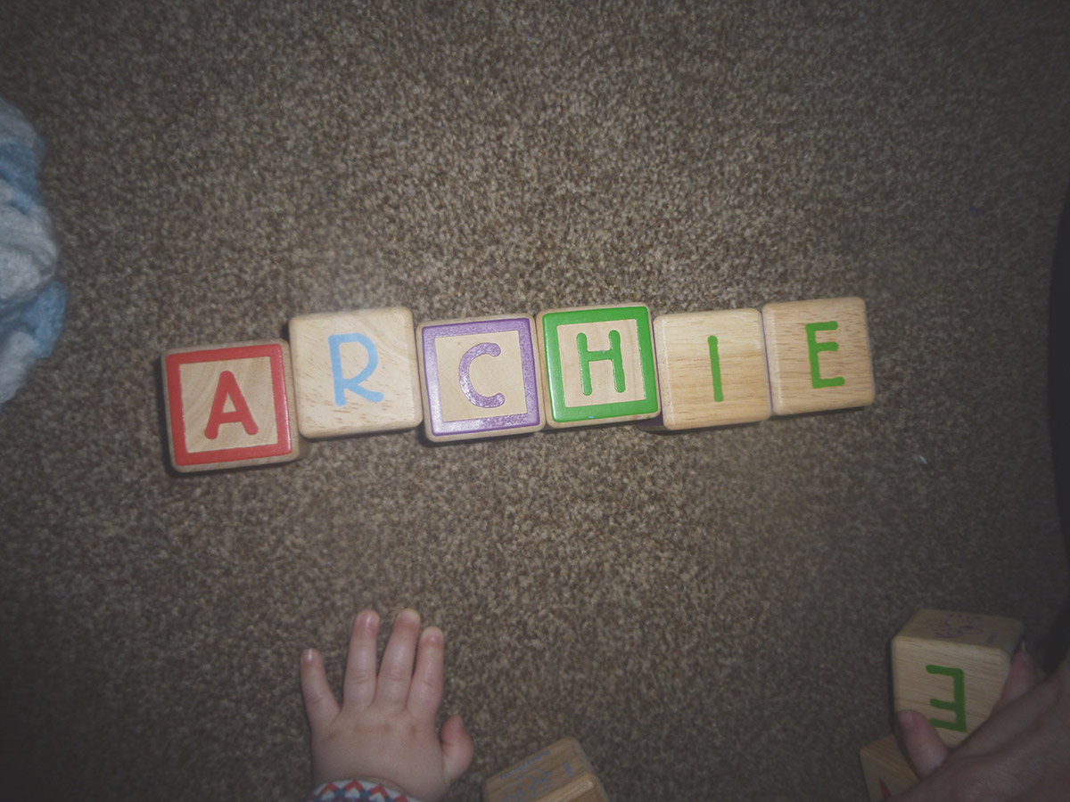 13 month old baby spelling out his name with wooden alphabet blocks