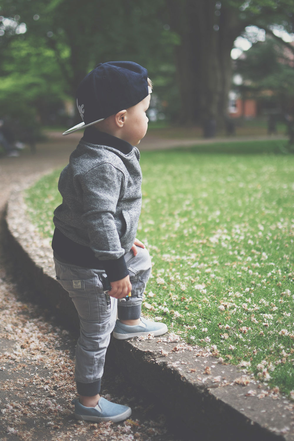 Fashion Friday; Grey slacks & baseball caps // 042 - Toddler wearing H&M 'ledge' suede baseball cap, H&M black 'super' lightweight jacket, Next rugby polo and grey trousers and H&M denim slip-ons having fun at the park in Spring