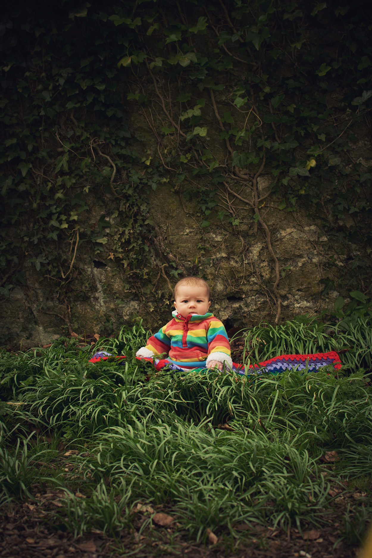 Oh, these two boys of mine.. - 3 year old and 7 month old brothers wearing rainbow Frugi fleece, Little Bird yellow wellies, Piccalilly dungarees and Joules red stripy hat sitting in the woods playing and exploring together