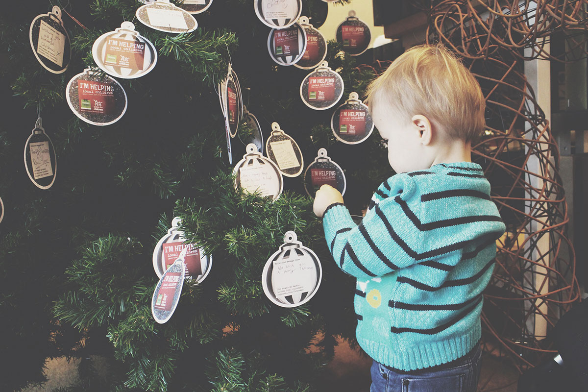 Toddler Fashion Tips & Hanging Baubles at Homesense - Toddler wearing a George dinosaur striped jumper, hanging a bauble for Action for Children with Homesense