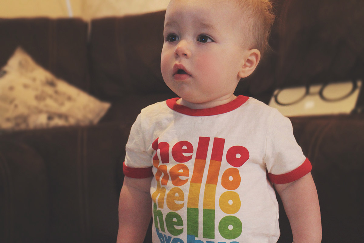 14 month old toddler wearing Little Bird t-shirt and Converse bottoms holding Winnie-the-Pooh comforter