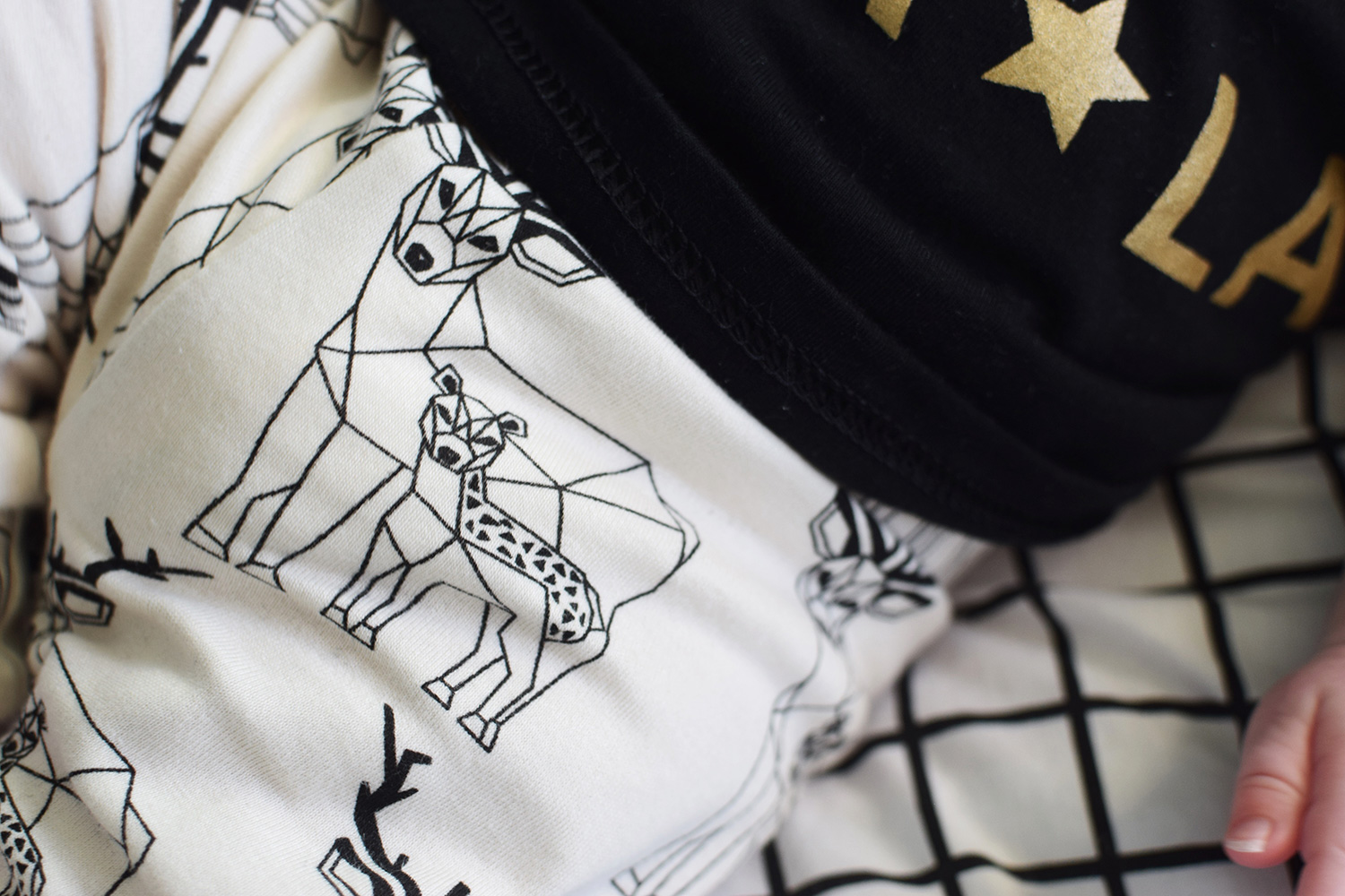 It's Christmassss with Tobias & the Bear {Fashion Friday 046} - Adorable 4 month old baby boy wearing 'Fa la la la la' Tobias & the Bear black and gold t-shirt, stag cream geometric leggings and H&M black bobble hat on grid duvet from Primark with white rabbit noodoll