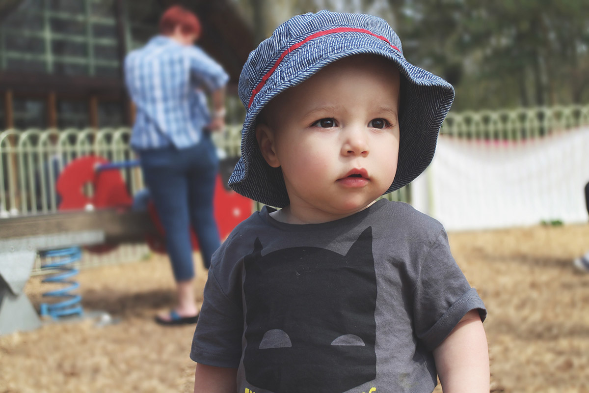 Toddler at the park wearing Mothercare hat and H&M Batman t-shirt