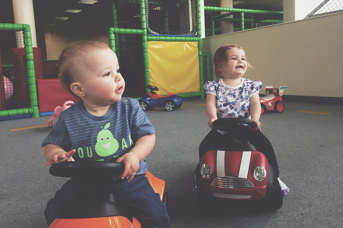 Toddler with friend sitting on cars at soft play