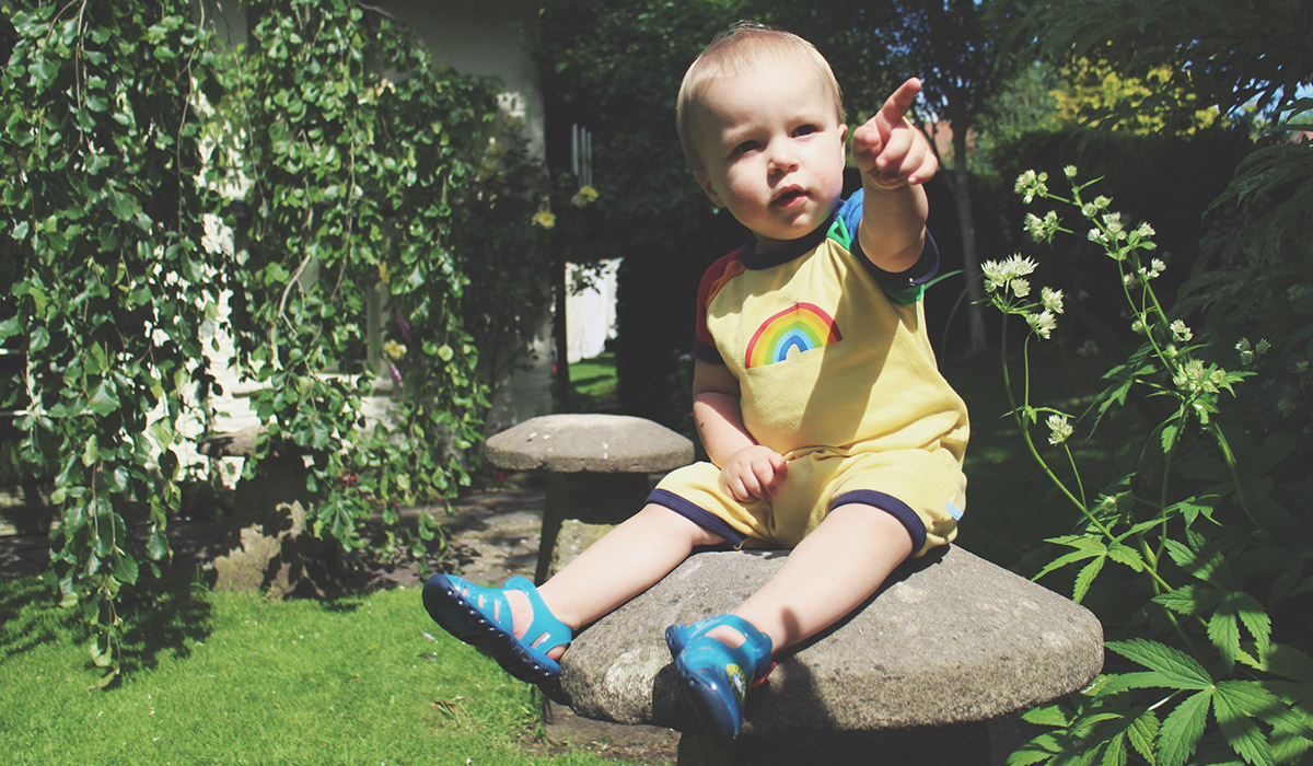 Fashion Friday // 025; He Talks To The Rainbows - Toddler wearing Little Bird rainbow romper and Thomas the Tank Engine jelly shoes sitting on garden toadstool