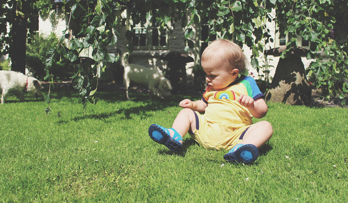 Fashion Friday // 025; He Talks To The Rainbows - Toddler wearing Little Bird retro rainbow romper and Thomas the Tank Engine jelly shoes sitting on grass