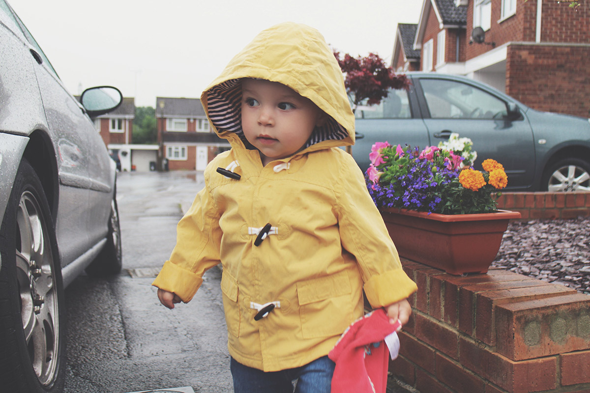 Fashion Friday // 028; & With Every Drop Of Rain, You Know I Love You More - Toddler wearing yellow raincoat from George standing in the rain