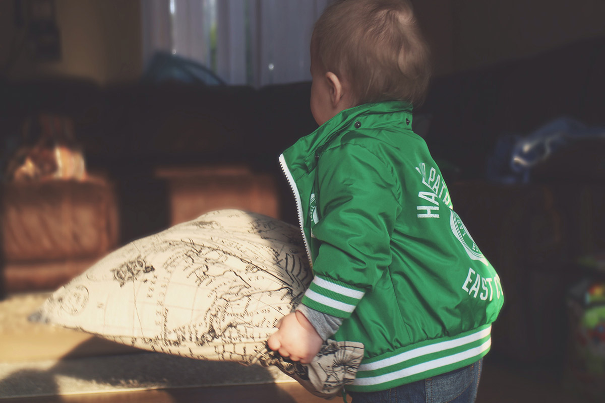Toddler wearing H&M green coat and M&Co converse shoes t-shirt