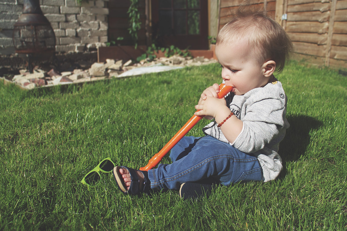 Fashion Friday // 021; Toddler wearing Zara camera jumper with Zara jeggings and H&M illuminous yellow sunglasses playing recorder in the garden