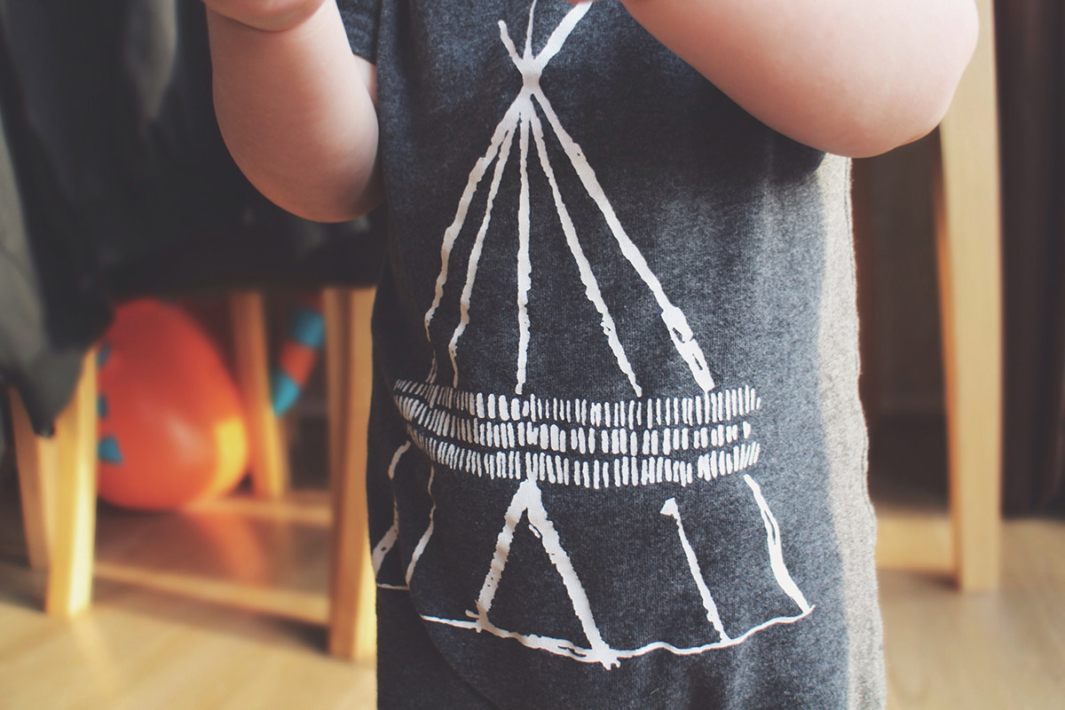 Toddler wearing Next teepee onesie and stripy hat