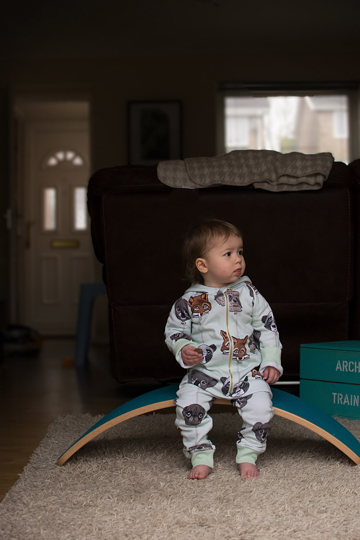 Two young brothers wearing Filemon Kid animal balloon and panda onesies playing with their Babi Pur bought ocean blue Wobbel Board at home - Organic, Scandi-inspired kid's fashion