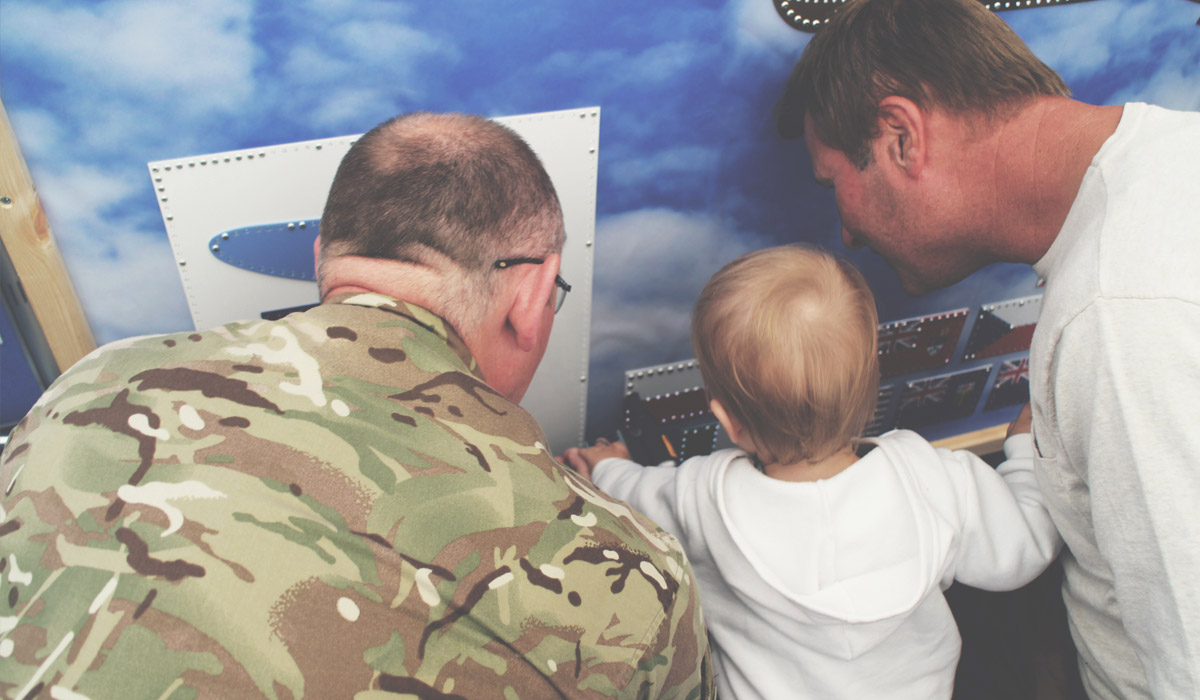 Toddlers' Day Out @ RAF Fairford Air Tattoo - 18 month old taking part and punching a pellet into display with RAF workers
