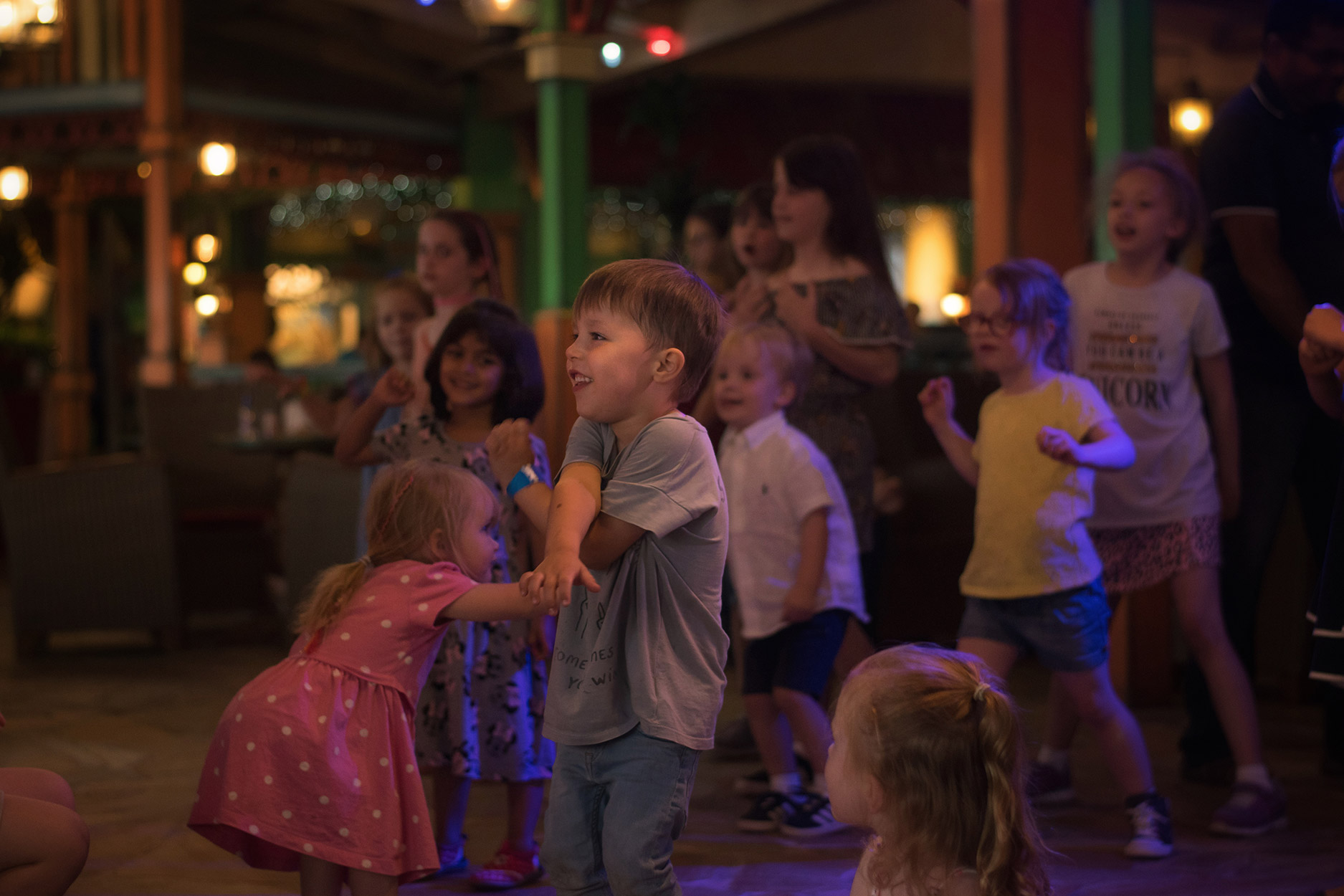 Pre-schooler wearing Bonnie Mob rainbow denim jacket dancing in the Splash Landings Hotel at Alton Towers Resort