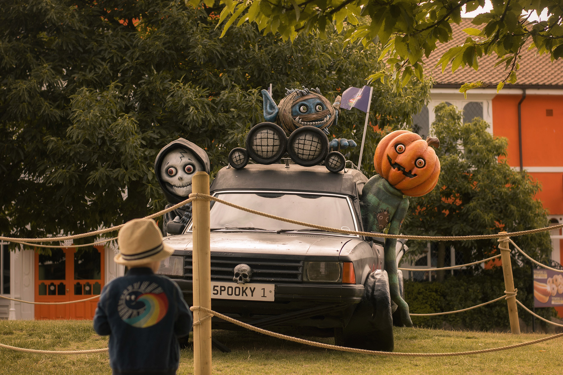 Pre-schooler boy wearing Bonnie Mob rainbow jacket looking at Halloween models and car with 'Spooky1' numberplate at Alton Towers Resort