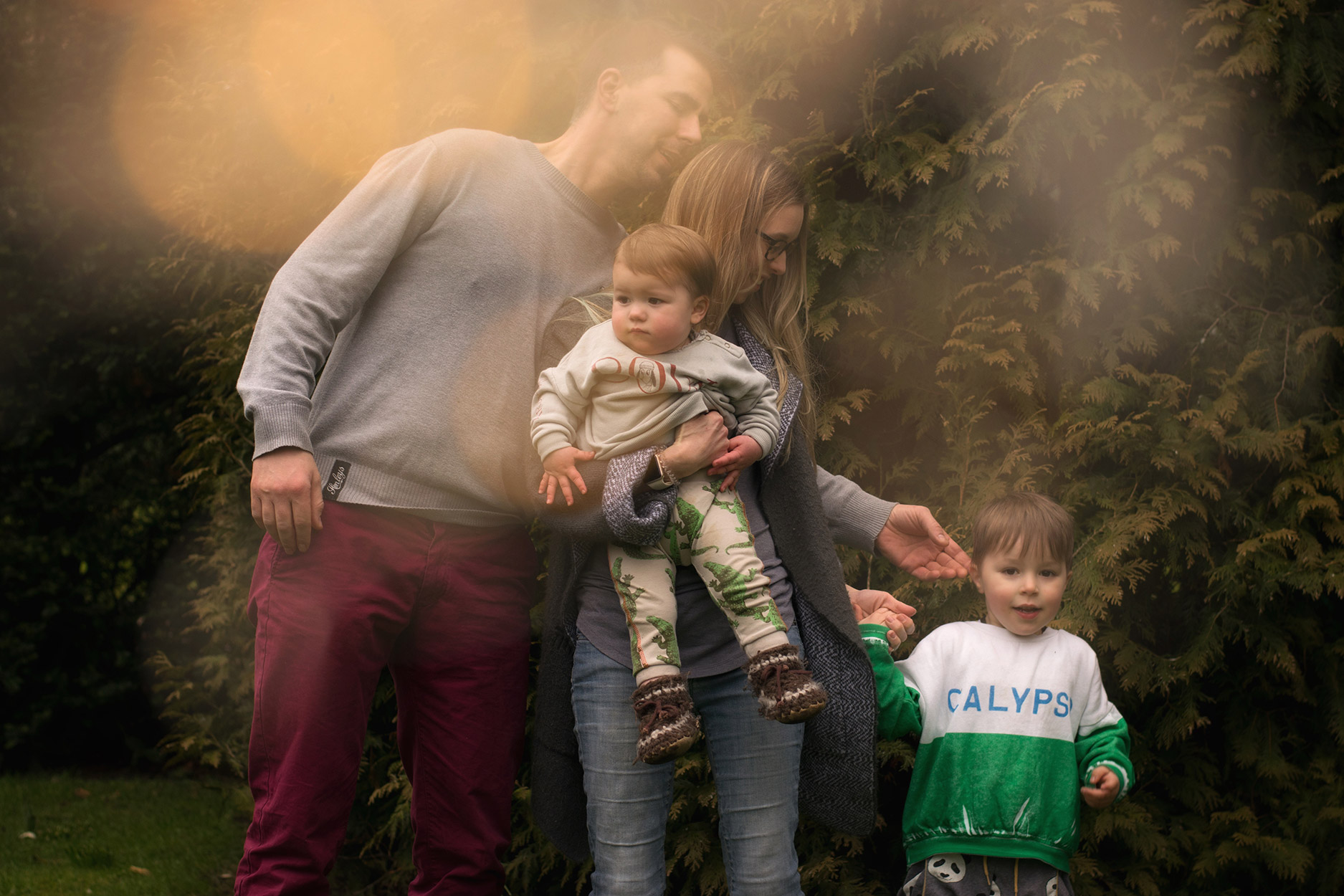 Family of four with two young brothers wearing Bobo Choses BOW and Calypso sweatshirts and Lamb & Bear crocs leggings for family photoshoot amongst snowdrops