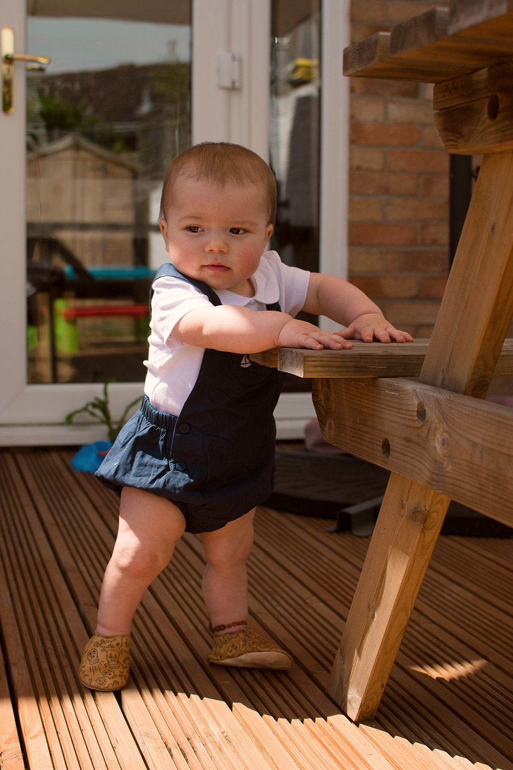 Baby Jesse Blue at 10 months old - Baby boy wearing cute sailor short vest and romper summer outfit and pirate leather shows standing at the table in the garden