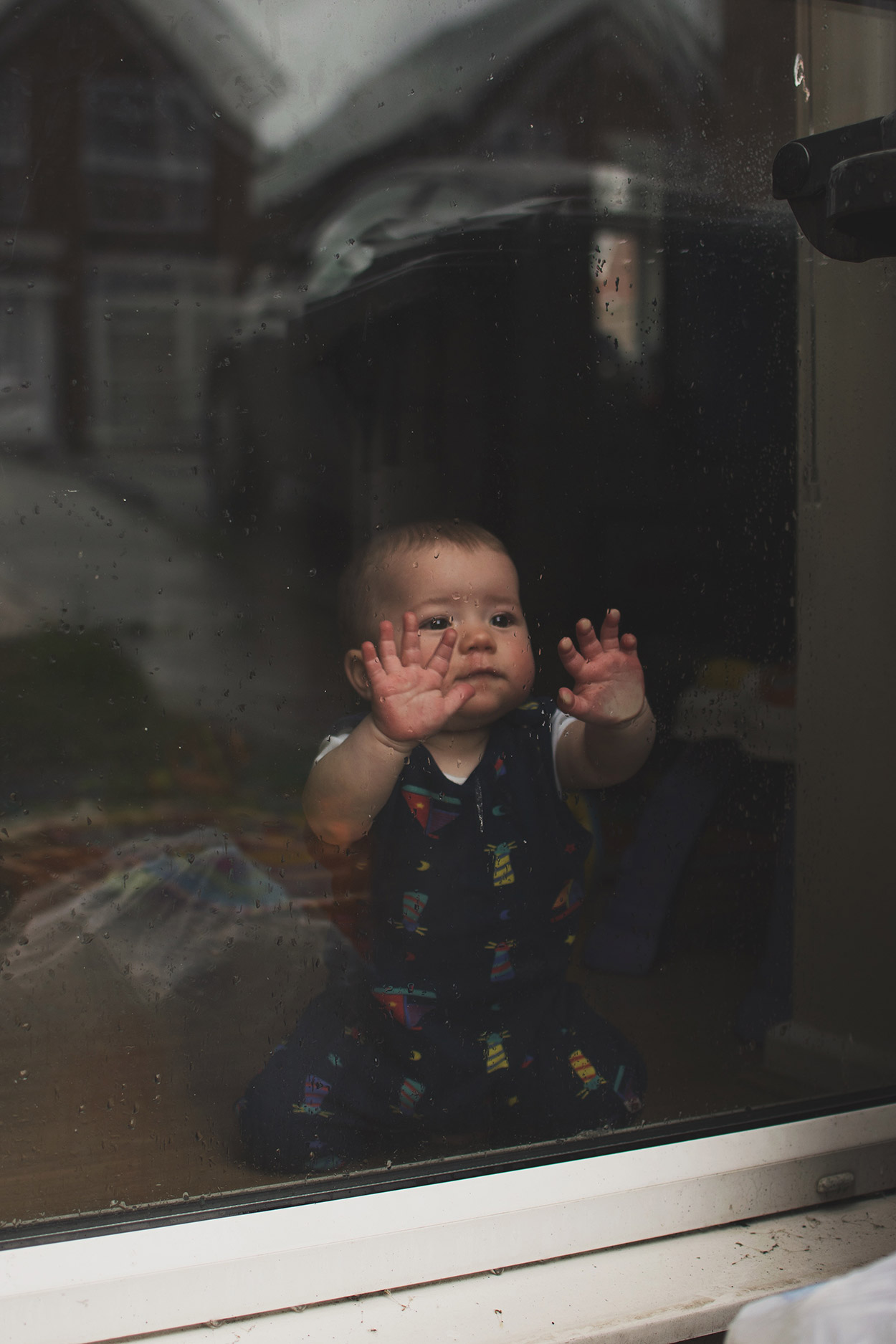 Baby Jesse Blue at 10 months old - Baby boy wearing Piccalilly lighthouse dungarees looking out of the window at Mother