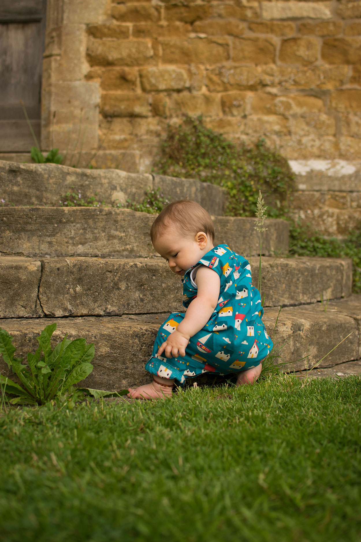 Baby Jesse Blue at 11 months old - Baby boy wearing Little Green Radicals sail away play away romper suit at Chastleton House National Trust gardens