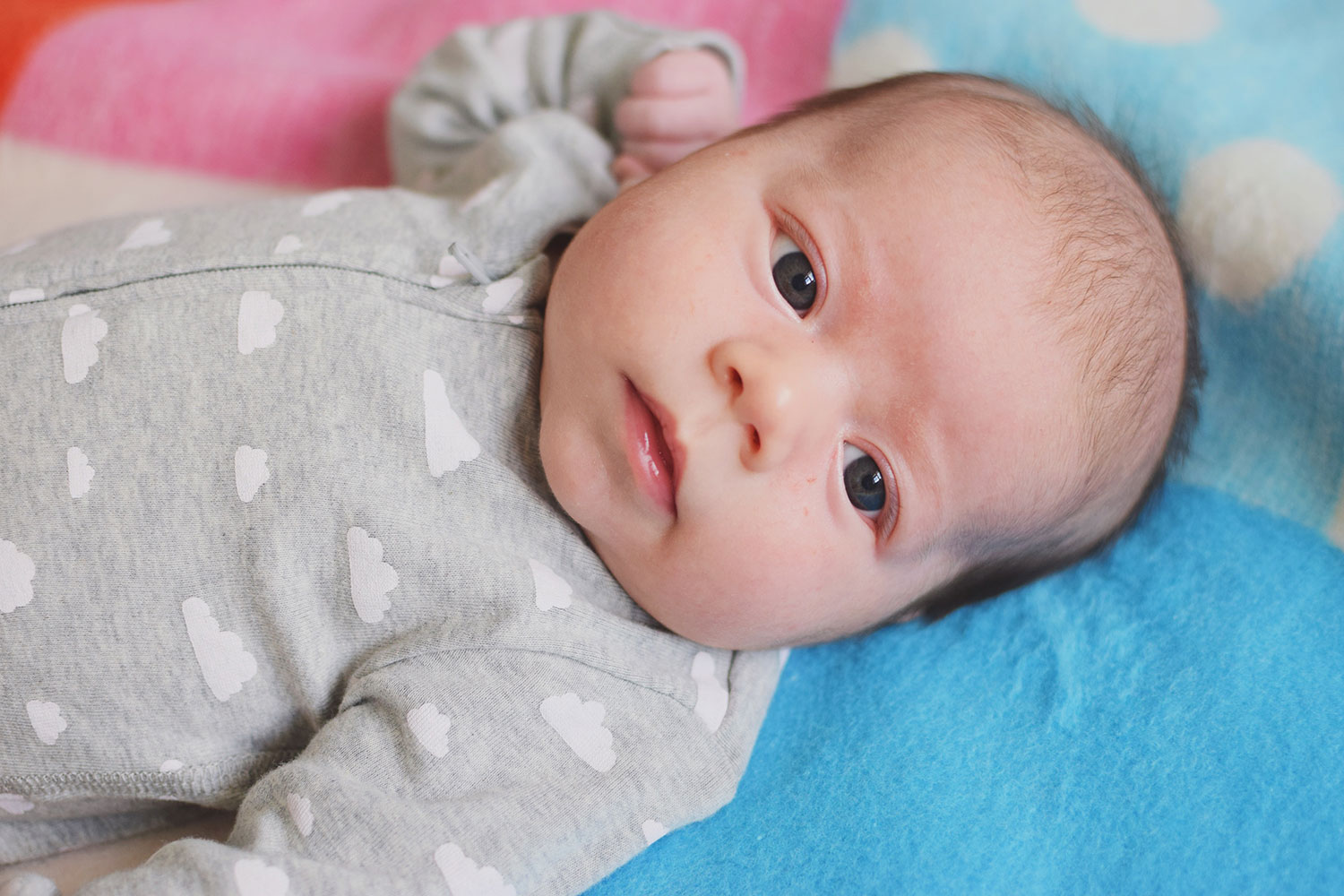 Baby Jesse Blue at 2 months old - Newborn wearing starry sleepsuit laying asleep on Primark patterned geometric duvet