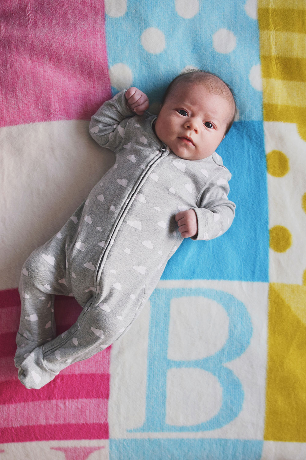 Baby Jesse Blue at 2 months old - Newborn smiling whilst laying on multicoloured alphabet blanket