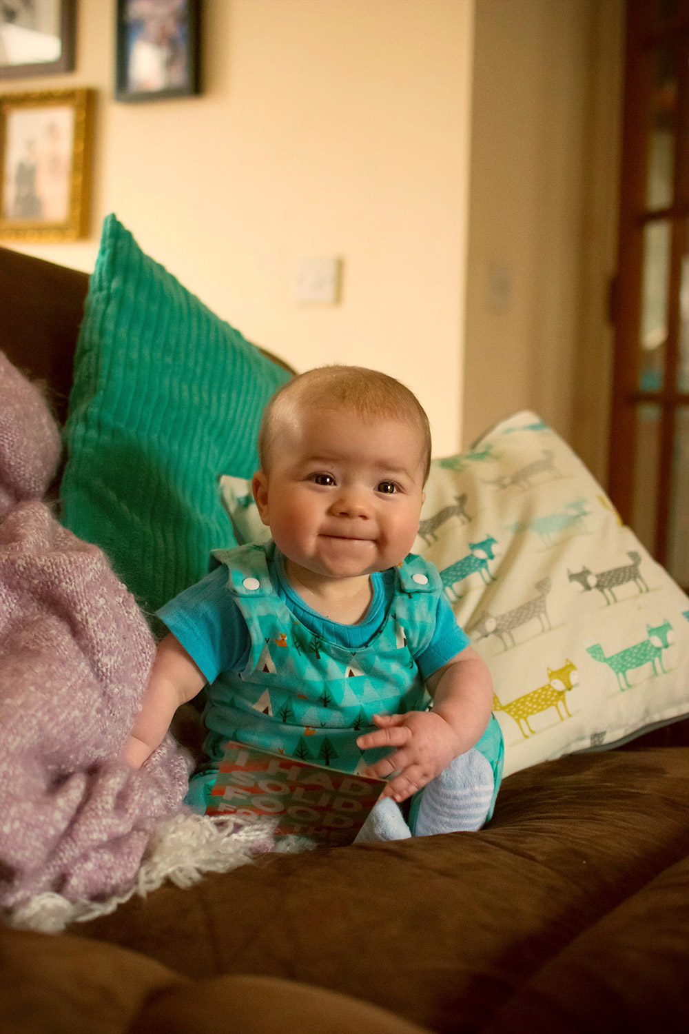 Baby Jesse Blue at 6 months old - Baby boy looking up at camera with huge brown eyes smiling and laughing