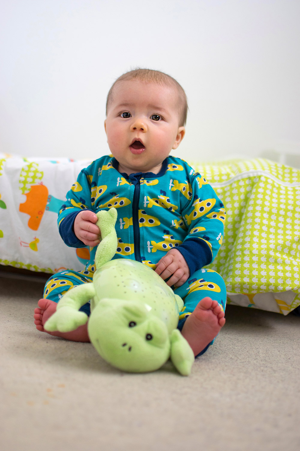 Baby Jesse Blue at 7 months old - Baby boy looking up at camera laughing and smiling wearing Frugi houses sleepsuit playing with Grimms rainbow tower